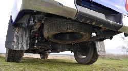 Bajos a lo 4x4 puro: enorme altura, eje rígido, ballestas y una rueda de repuesto de verdad colgada y anclada con cadena
