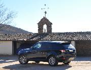 El Range Rover Sport recibe la bendición de una Virgen muy chiquitita subida en lo alto de un tejado.